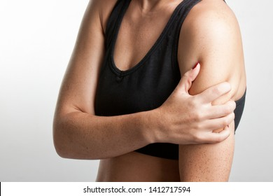 Female with pain in her arm, isolated in a grey background