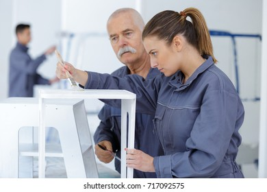female painter focused at worker
