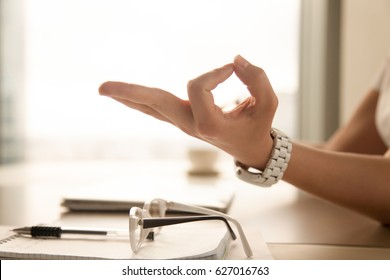 Female palm with fingers folded in Jnana mudra gesture from eastern spiritual practices. Businesswoman relaxing at the table in office. Meditating at workplace, getting peaceful mind concept. Close up