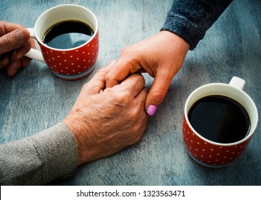 Female palm in the hand of an elderly man, at a table with coffee. Psychological support concept