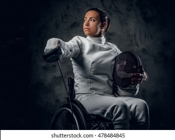 Female paralympic wheelchair fencer in studio.