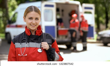 Female paramedic smiling into camera, ambulance crew blurred on background