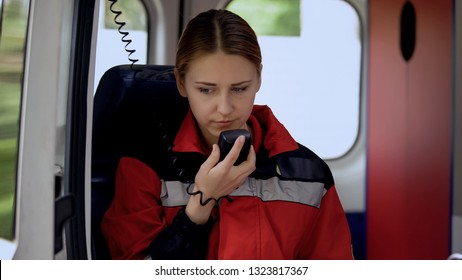 Female paramedic talking by radio in ambulance, ready to drive out on call