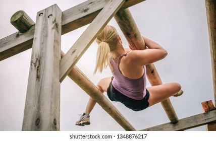 Female participant in a obstacle course doing weaver obstacle