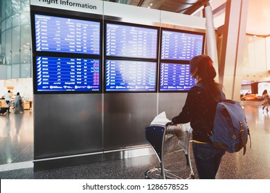 Female passenger at the airport looking at the flight information board