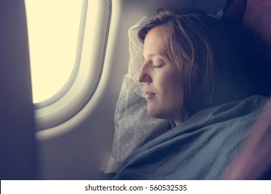 Female passenger sleeping covered with blanket.