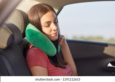 Female passenger sleeps in car while rides on long distance, uses small pillow as has pain in neck, takes nap, has rest, feels tired for being in motion much time. People and travelling concept
