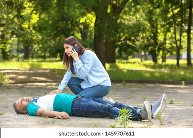 Female passer-by calling an ambulance for unconscious mature man outdoors
