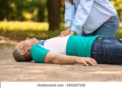 Female passer-by doing CPR on unconscious mature man outdoors