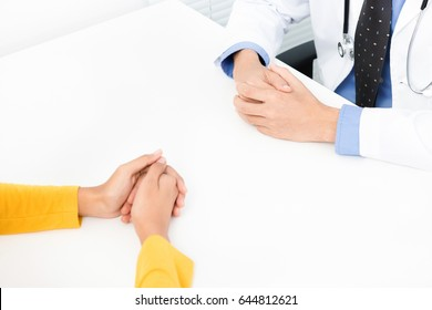 Female patient consulting with doctor at the table in the office