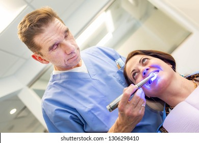 female patient at dentis teeth whitening procedure with ultraviolet light UV lamp.