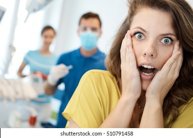 Female patient frightened from treatment at dentist's surgery.