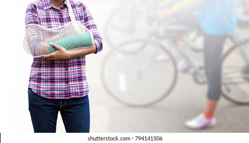 Female patient with green cast on arm isolated on blurred background woman riding a bicycle, body injury concept.