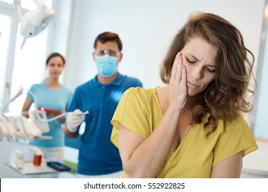 Female patient having toothache at dentist's surgery.