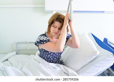 Female patient holding on to a device for lifting in hospital room