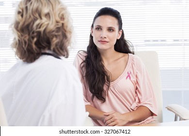 Female patient listening to doctor with concentration in medical office against pink awareness ribbon