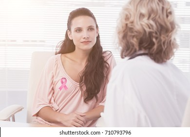 Female patient listening to doctor with concentration in medical office against breast cancer awareness ribbon