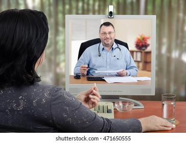 Female patient looks at virtual doctor in the monitor. Mature woman holds a pill by hand and ready to take it. Doctor with glasses and a stethoscope reviews medical laboratory results with her.