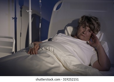 Female patient lying in bed and worrying about her health