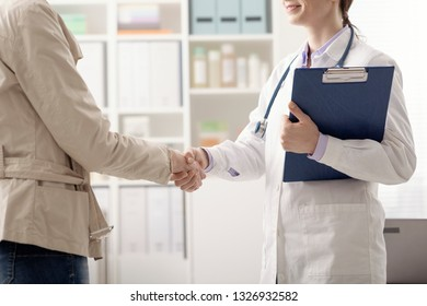 Female patient meeting the doctor in the office, they are shaking hands and greeting