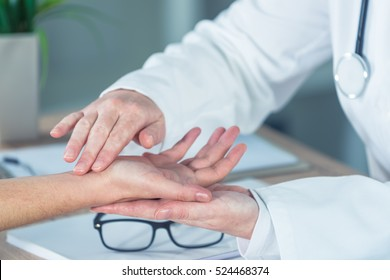 Female patient at orthopedic medical exam in doctor's hospital office, traumatology and medical consultation for hand wrist injury