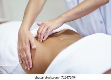 Female patient is receiving treatment by professional osteopathy therapist. Woman receiving a belly massage at spa salon