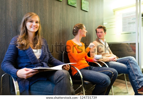 Female patient at reception of clinic looking at the viewer, in the background other people waiting for her treatment