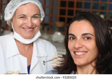 Female patient smiling while dentist with the equipment in the back