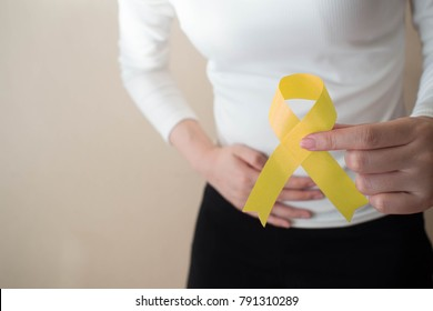 Female patient suffering form abdominal pain and holding yellow ribbon awareness symbol for endometriosis, bladder cancer and liver cancer concept. Health care and medical. Copy space.