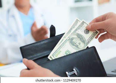 Female patient takes out of her wallet hundred dollar bills to pay for the services of a doctor. Bribery and corruption in Health Care Industry.