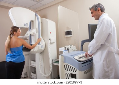 Female patient undergoing scan at mammography machine with male doctor supervisor. Happy hospital scene.