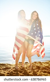 Female patriots with national American flag having fun on the beach