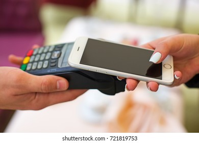 Female paying with NFC technology on smart phone, hands close up. Woman using mobile phone for pay by the bill.