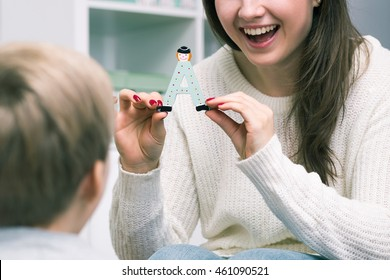 "Female pedagogue is showing to her pupil a letter ""A"""