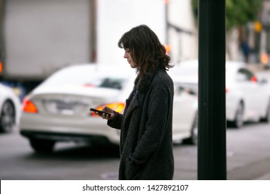 Female pedestrian waiting for a rideshare.  She is sharing her gps location via cellphone app so the driver can pick her up in the city.  Cars are blurred to obscure make model and license plates.