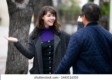 Female pedestrian walking into a friend by coincidence on the street.  They are meeting and greeting each other outdoors in a city or a park. Two people looked surprised.