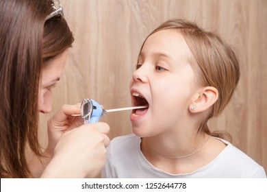 Female pediatrician or health care practitioner examines elementary age girl's throat using wooden tongue depressor and torch. Child physical examination concept