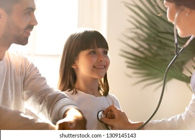 Female pediatrician holding stethoscope examining happy child girl visiting doctor with father, nurse checking heart lungs of kid doing pediatric checkup in hospital, children medical insurance care