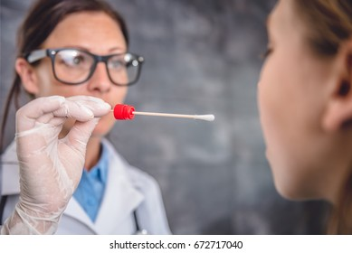 Female pediatrician using a swab to take a sample from a patient's throat