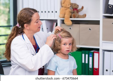 female pediatrician in white lab coat examined little girl for lice