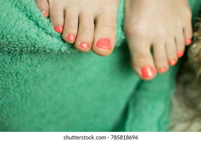 Female pedicure on a green textile background.