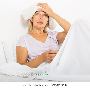 female pensioner laying in bed with headache