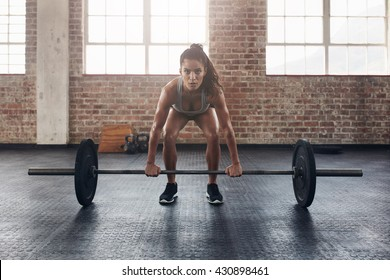 Female performing deadlift exercise with weight bar. Confident young woman doing weight lifting workout at gym.
