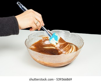 Female person blending chocolate gently with Gogl-Mogl, in a glass bowl on white table towards black