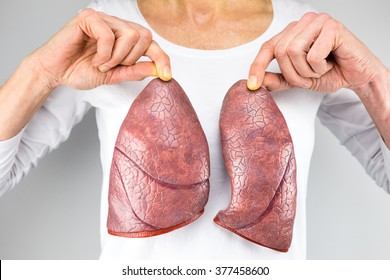 female person holding two artificial models of lungs in front of body with white shirt