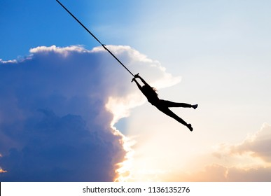 female person silhouette flying in sky, silhouette girl flying on a rope, human  female gymnast hanging on rope against the background of clouds and sunset