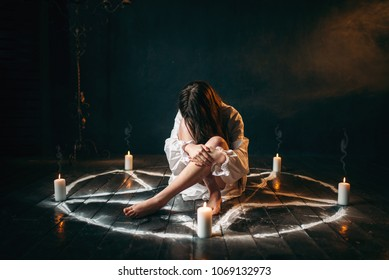 Female person sitting in pentagram circle, magic