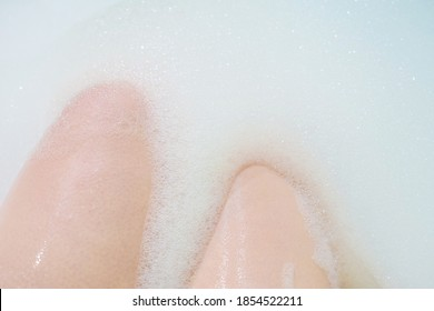 Female person washing herself. Woman legs covered by soap bubbles bathwater in white bathtub, skin care