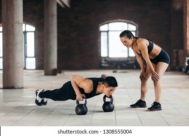 female personal trainer controlling a man who is doing push ups with kettlebells. woman encourages her boyfriend to go in for sport