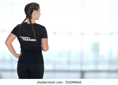 Female Personal Trainer, with his back facing the camera, in a gym